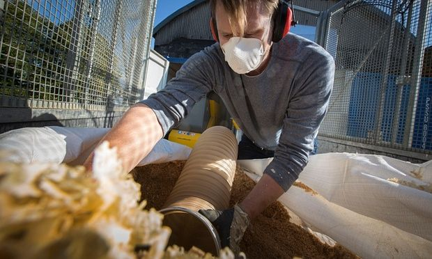 David Ousby, director of Cambridge Wood Fuel, vacuuming joinery workshop dust and shavings for briquettes.