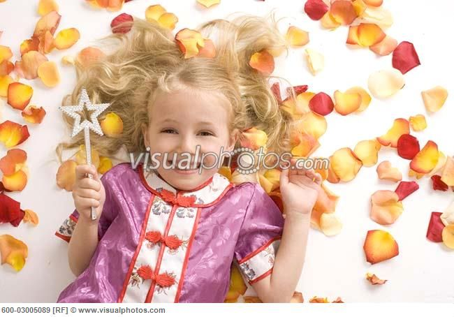 Little Girl with Magic Wand Lying Amongst Flower Petals