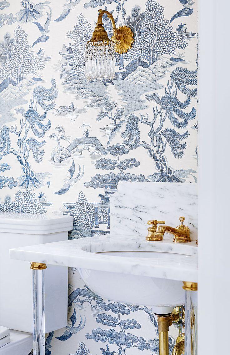 a Calacatta marble washstand sink with glass legs is an elegant showpiece that still keeps the chinoiserie grasscloth wallpaper at centre stage. the exposed plumbing and vintage sconce (original to the home) bring a warm brassy hue into play.