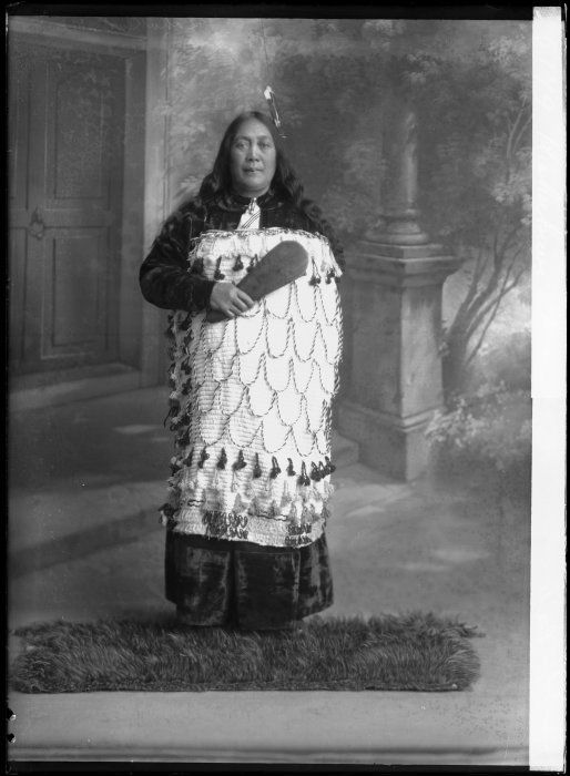 Maori woman with a kiwi feather cloak at her feetStanding portrait of an unidentified Maori woman photographed circa 1900 by Frank J Denton of Wanganui. She wears a white tipped feather in her hair, a full length frock with a brooch at the collar, and a Maori cloak decorated with tassles. At her feet is a kahu kiwi (kiwi feather cloak). She stands in front of a painted backdrop.