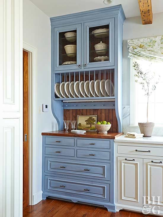 A rich blue cabinet—designed to look like a freestanding hutch—adds a touch of color to an otherwise cream-and-brown kitchen color scheme. Blue cabinetry is inherently calming yet stands out from neutral surroundings. Paint Color: Benjamin Moore, New Hope Gray.