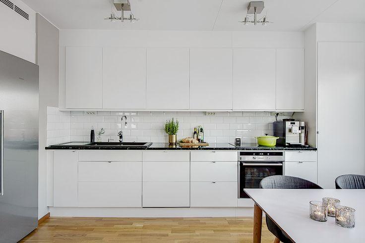 Stilrent kök från Ballingslöv med bra bänkytor för matlagning och skåp. Släta vita luckor, bänkskiva i stilren mörk sten och med dubbla hoar i svart komposit. Induktionshäll och samt infälld varmlyftsugn med pyrolysfunktion.