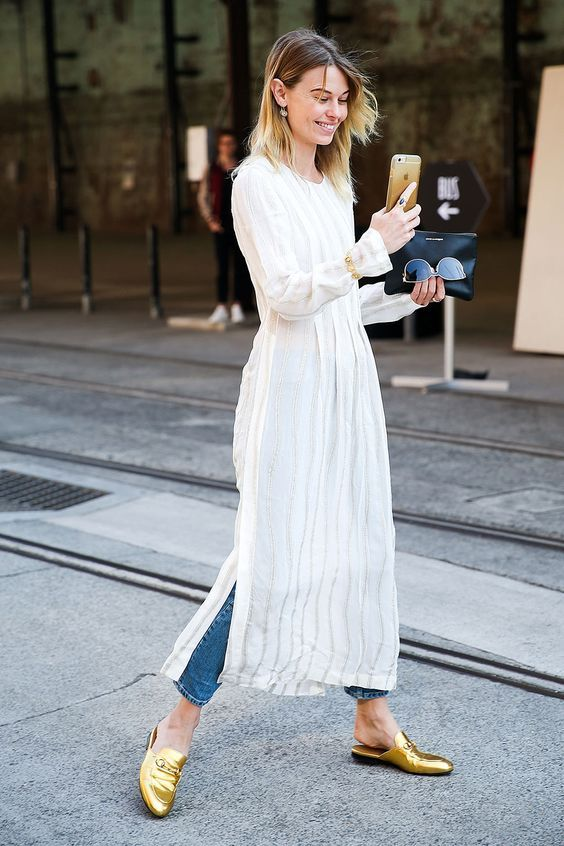 Pair a long white tunic over jeans with gold statement loafers for effortlessly fashion-forward street style.