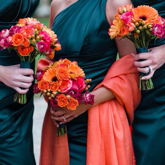 Dark teal bridesmaids saris with bold two-tone orange and gold bouquets.