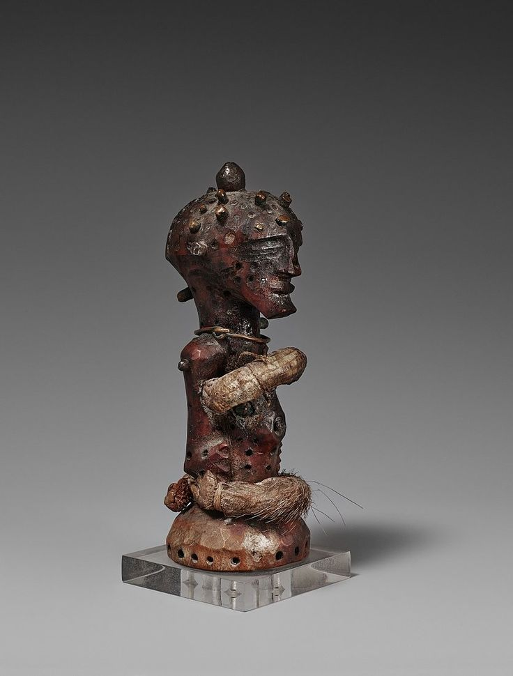 A SMALL SONGYE POWER HALF FIGURE  Democratic Republic of the Congo  14 cm. high  Nkisi, standing with the arms in relief, the body and head pierced all over for the insertion of copper nails, several of which remain, fetish cavity in the abdomen, iron spike in the top of the head, a bundles of fetish material wrapped in skin about the chest and waist, plaited fibre band about the waist, copper ring about the neck, dark reddish brown patina.  Provenance:  Ludwig Bretschneider, Munich