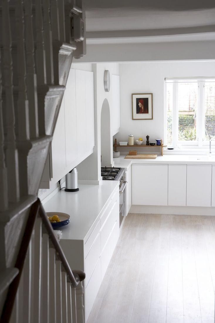 Love how the stove is integrated into the old fireplace. White Corian counter, Kitchen in Victorian house in Stoke Newington, London | Remodelista