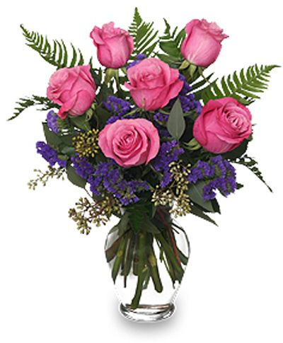 A half dozen pink roses arranged in a clear glass vase.  Available in other colors.