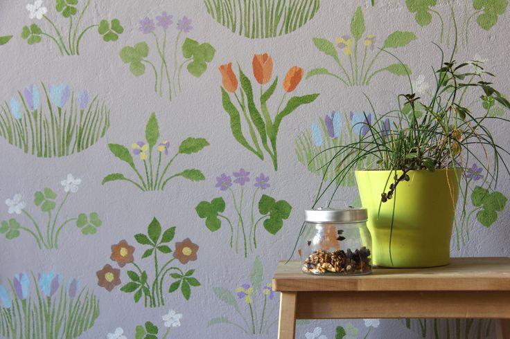 Šablonová malba na stěně, vzor Jarní zahrada. Vícebarevná šablona na šedém podkladu. / Pattern painting on the wall called Spring garden.