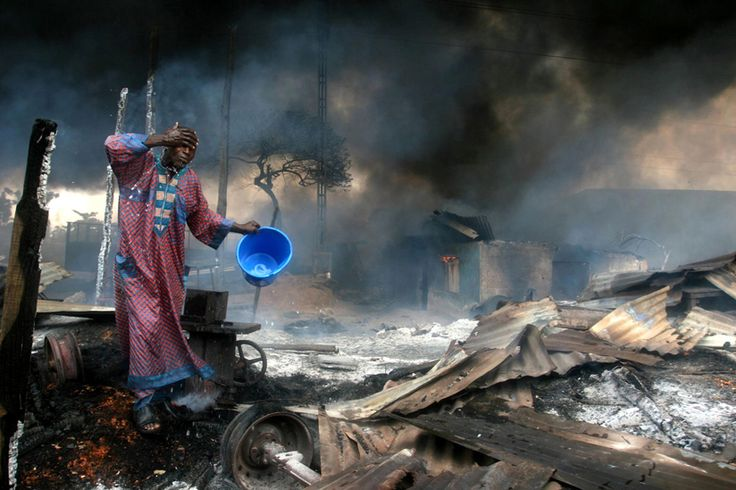 © Akintunde Akinleye, 2006, from the series 'A Vanishing Wetland', Lagos / Nigeria  'A man rinses soot from his face at the scene of a petrol pipeline explosion. At least 260 people were killed after a punctured pipeline caught fire. Thieves had tapped it to fill tankers with petrol for resale, and hundreds of people had gone to the scene to scoop up leaking fuel in plastic containers. Pipeline vandalism and fuel theft are common in Nigeria, the world's eighth largest exporter of oil, where…