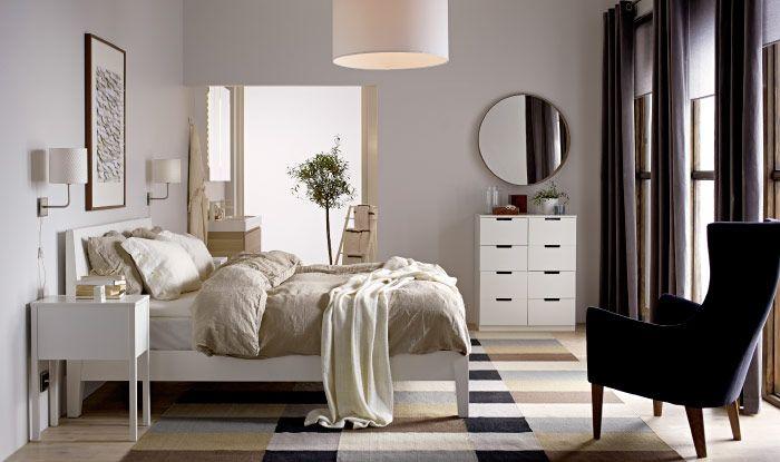 Ložnice pískové barvy s bílým úložným nábytkem, tmavou židlí a stropní lampou.