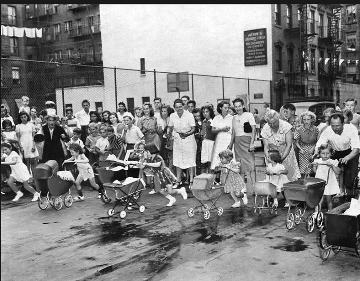"""from the bettman/corbis archive..august of 1940. the annual """"anything on wheels"""" eastside doll carriage race open to girls from ages 2 1/2 to 7 with their parents and over 150 people cheering them on. the winner was roberta morton age 7 of 627 east 16th street. her prize was a huge baby doll (naturally). if she's still with us... roberta would be 82 today."""