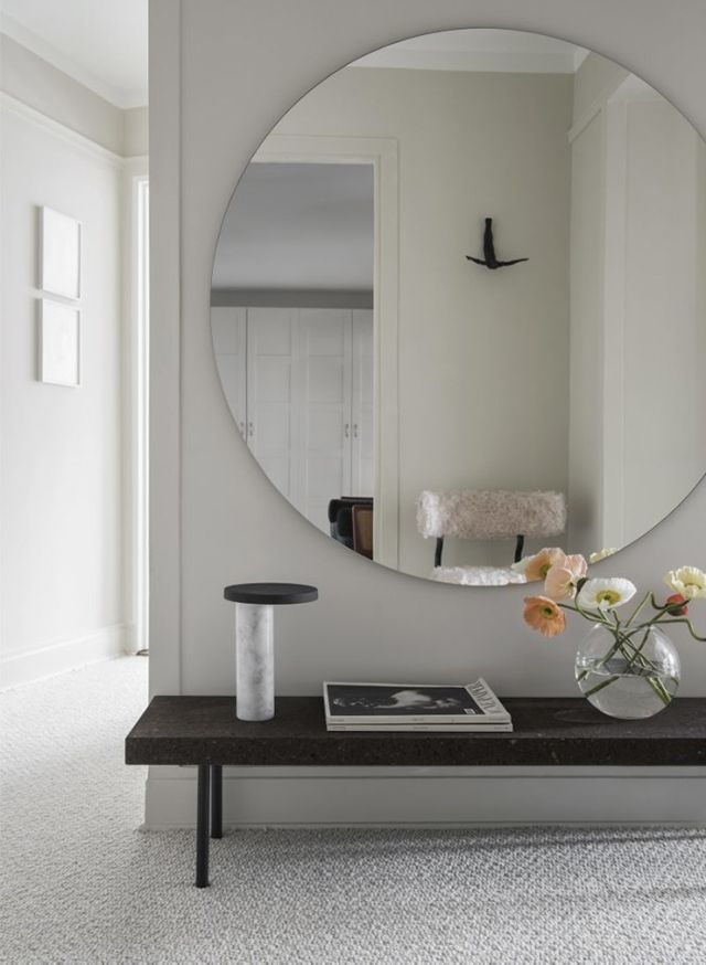 Entryway with giant circular mirror and flowers