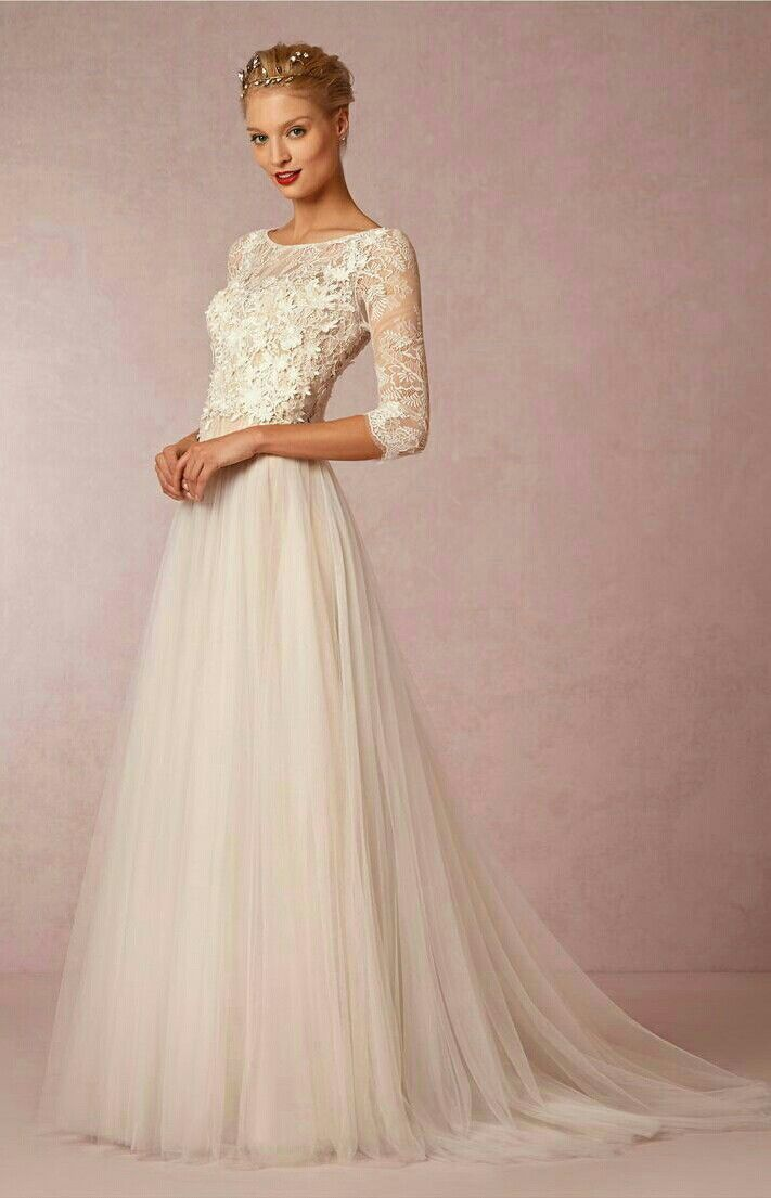 Watters trouwjurk met lange mouwen. Deze bruidsjurk heeft een mooi bewerkte kanten top en een luchtige tule rok.