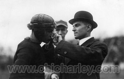 East High School football coach Frank Gullum adjusts Chic Harley's helmet chin strap during game circa 1913.