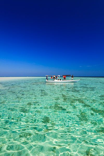 Tourist boats in the crystal clear waters around the small island of Pulau Geleang, located within the Marine National Park of Karimunjawa or Karimun Jawa, which translates as a stone's throw from Java.