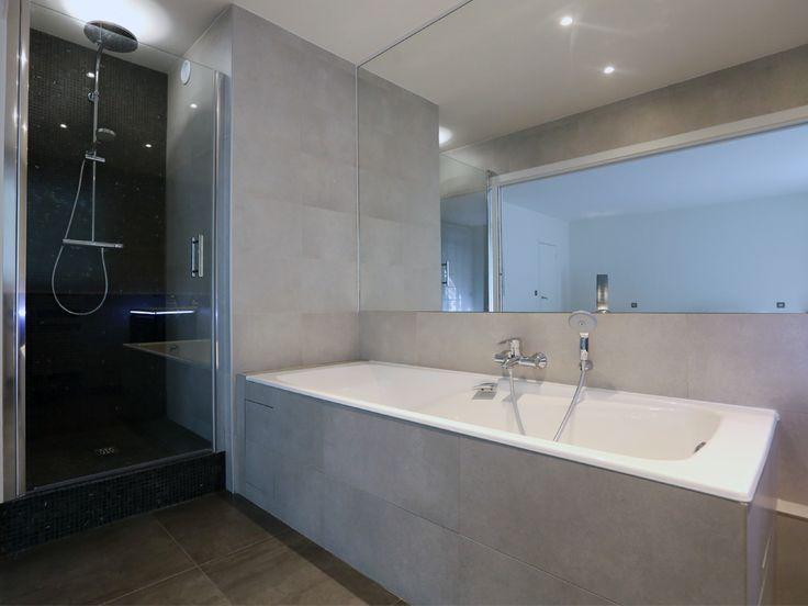Un grand miroir, d'un seul tenant, recouvre le mur principal. La douche est en partie recouverte de mosaïques de marbre noires. Le carrelage est anthracite au sol (60x60cm) et gris au murs(30x60 cm). Très lumineuse, elle est ouverte vers l'extérieur grâce à une fenêtre et sur le reste de l'appartement via une porte double encastrée. - Modern and design bathroom. A large mirror covers the main wall. The shower is covered with black mosaics . - Xavier Lemoine Architecte d'Intérieur Paris 17-