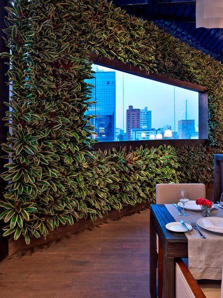 Restaurante projetado pela arquiteta Mariana Correia com parede verde da CP Paisagismo