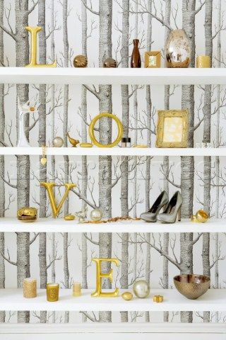 Still life with tree silhouette wallpaper and gilt letters  on a white shelf with group of metallic