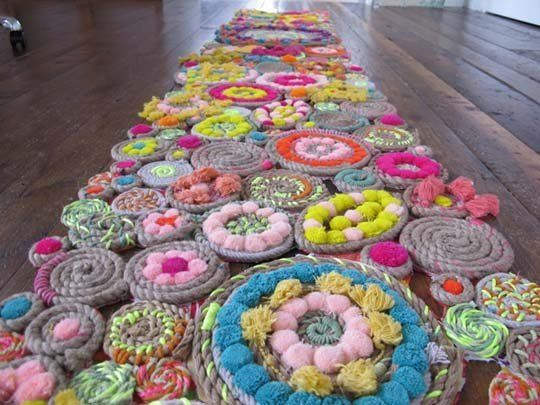 I am obsessed with DIY rugs. It's incredibly difficult to make a rug that is durable, provides some cushioning, is cheap and easy to make, and looks good. This rope and pom pom rug gets the gold medal in each category.