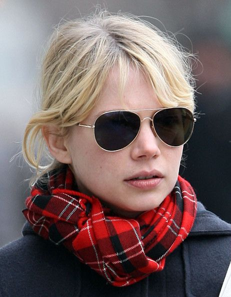 Round faces have soft curves with almost equal width and length.  To downplay roundness, choose frames with straight or angular lines (think rectangles and squares).  Classic colors like black and tortoise shell can minimize fullness by accentuating the lines of the glasses.  Thin metal frames (like the ones worn by Michelle Williams) are also a great option since they draw the attention toward the center of the face.