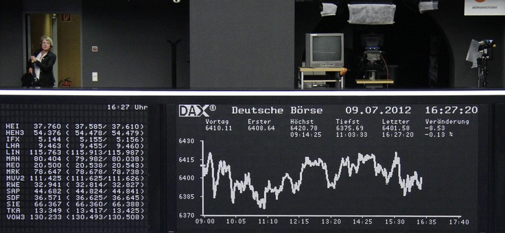 Woman stands at balcony next to DAX board at Frankfurt stock exchange