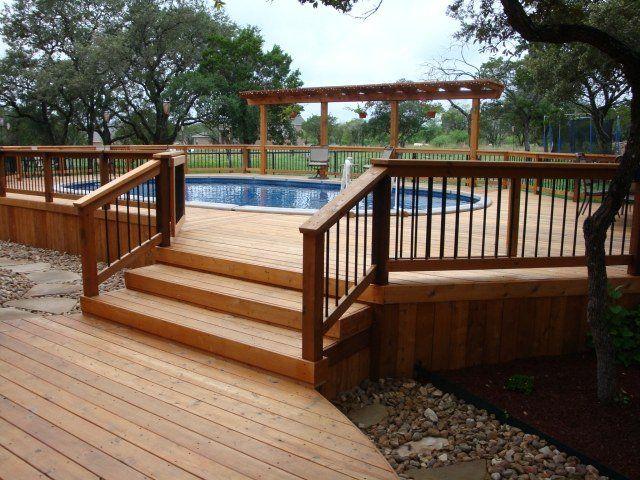 une piscine hors sol en bois ovale et grande sur la terrasse en bois