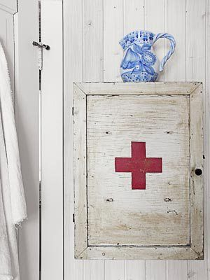 White board walls, blue and white pitcher, and vintage-style medicine cabinet.