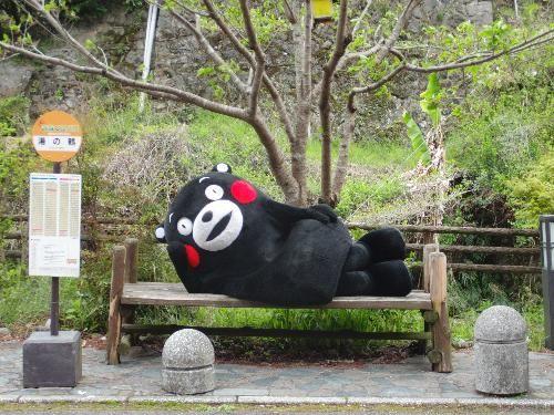Kumamon, lounging on a bench.