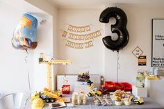 Une sweet table d'anniversaire pour un petit garçon avec comme décor une grue des camions jaunes et des casques de chantier