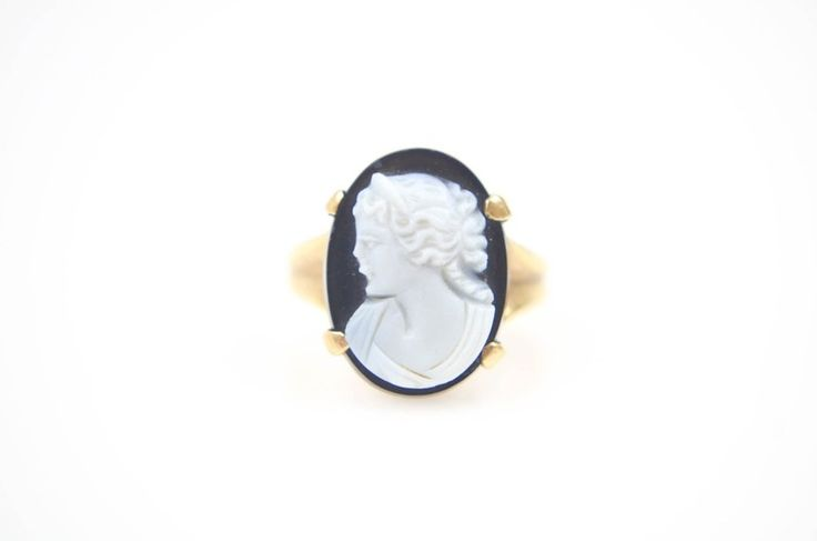A 10K yellow gold onyx cameo ring depicting a woman in Grecian style hair and clothing. Metal Type: 10K Gold Hallmarks: 10K Total Weight: 2.6 dwt Ring Size: 4.25 CENTER STONE Count and Type: 1 Onyx  Shape: Cameo Dimensions: 16 X 12 mm