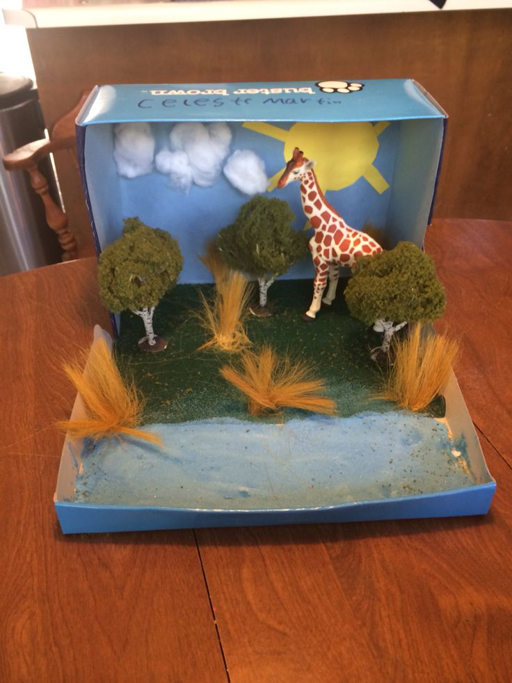 Giraffe habitat African Savanna diarama made with a shoe box, Construction paper, craft glue, super glue, cotton balls, colored sand, fake trees and grass from craft store