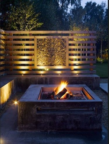 Square fire pit with grill and built in seating. The panelled wall being the bench makes the area appear cozy like an outdoor lounge room