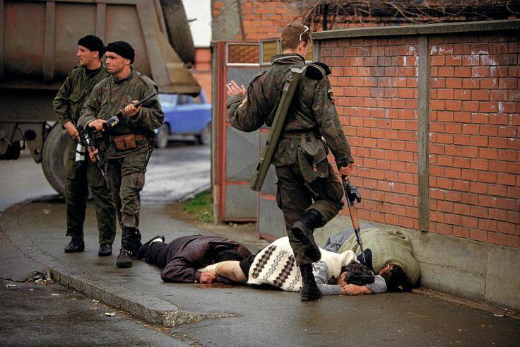Les Tigres d'Arkan donnent des coups de pieds à des civils bosniaques musulmans qu'ils viennent de tuer à Bijeljina, Bosnie, le 31 mars 1992. Photo Ron Haviv