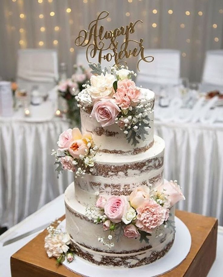 Pastel three tier naked wedding cake with blush flowers and gold cake topper