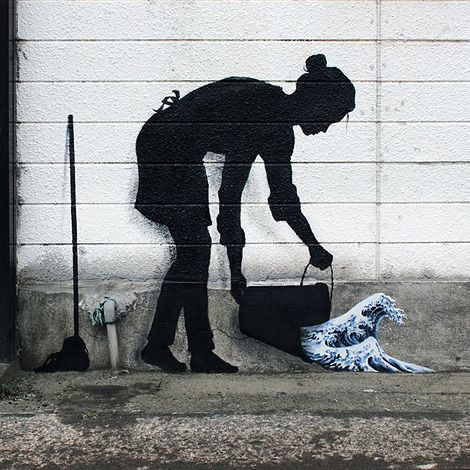 """Silhouette of a cleaning lady pouring out a bucket of Hokusai's iconic """"The Great Wave Off Kanagawa"""" left by Spanish street artist Pejac, appropriately in Kanagawa."""