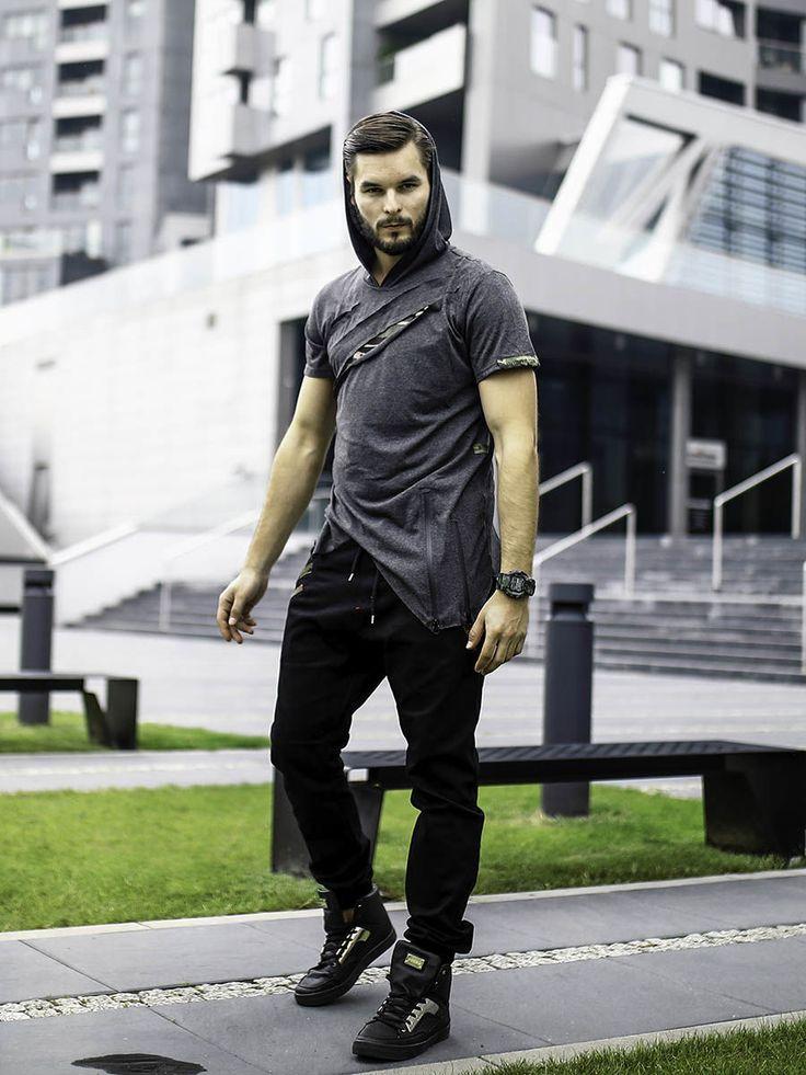 Bardzo wyrazista stylizacja od Denley dla wymagających. Koszulka jest nietypowa. Ma kaptur, surowe rozcięcia ze wstawkami w moro i asymetryczny dół. Look znakomicie dopełniają czarne joggery, wygodne sneakersy i sportowy zegarek.