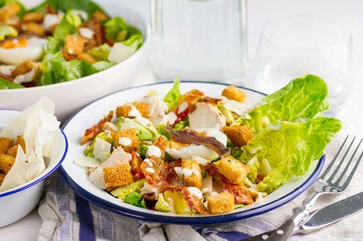 Recept voor caesar salad 2.0 voor 4 personen. Met zout, olijfolie, peper, bakpapier, kipreepje, ontbijtspek, wit brood, parmezaanse kaas, ei, avocado, mini romanasla, cherrytomaat, ansjovis, caesar sladressing en yoghurt