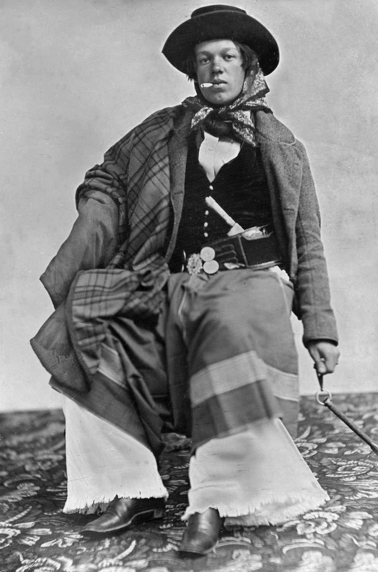 Gaucho in authentic habiliments, including poncho, greatcoat, bombachas, chiripá, wide leather belt festooned with silver coins known as a rastra, long-bladed facon knife, and a rebenque whip.