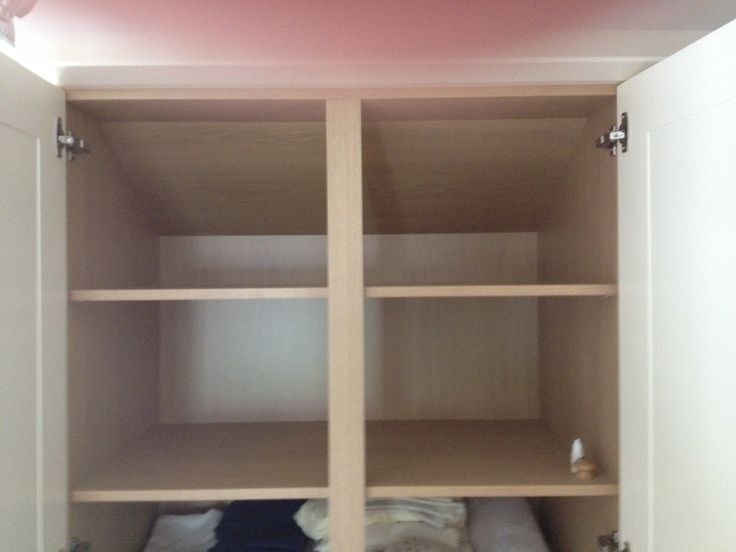 Cream wardrobe embedded into wall, utilizing all space possible. Practical storage arrangements.