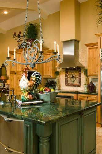 FRENCH COUNTRY KITCHEN ~ Chandelier in forged iron with a verdigris patina, old bronze faucets, and a beautiful ceramic French Coq  gives this spacious bright kitchen a true French country ambiance.