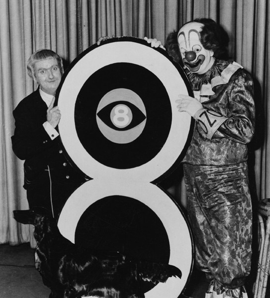 Captain Kangaroo and Bozo The Clown pose with a dog and with the logo of WJW-TV