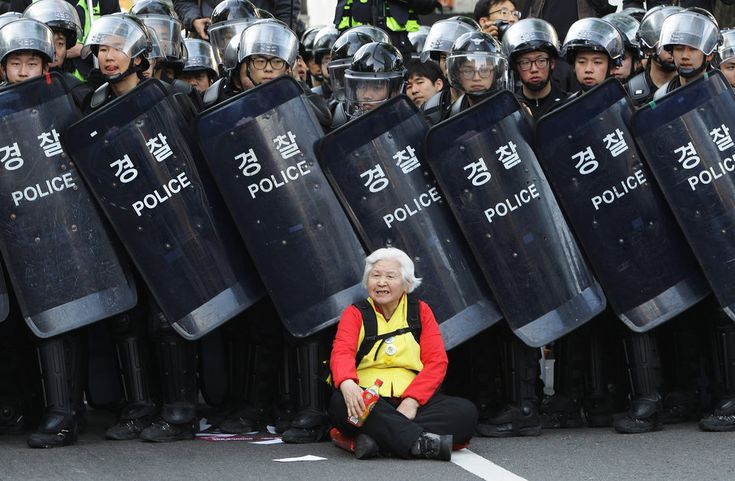 A woman sits in front of riot police blocking the road to protect protesters during the anti-government protest on April 24, 2015 in Seoul, South Korea.