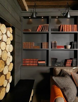 dramatic dark living room with dark painted built-ins, awesome lighting, and stacked firewood
