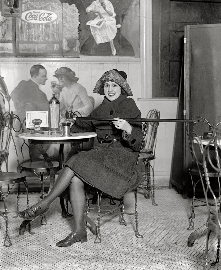 "February 13, 1922. Washington, D.C. ""Unidentified woman."" Demonstrating an ingenious Prohibition-era fashion accessory: the cane-flask."