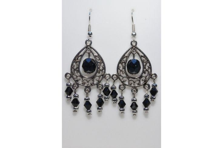 Boucles d'oreille en métal argenté montées sur un connecteur style bohème, perles noirs à facettes, perles cristal noir et perles argentées ondulées.
