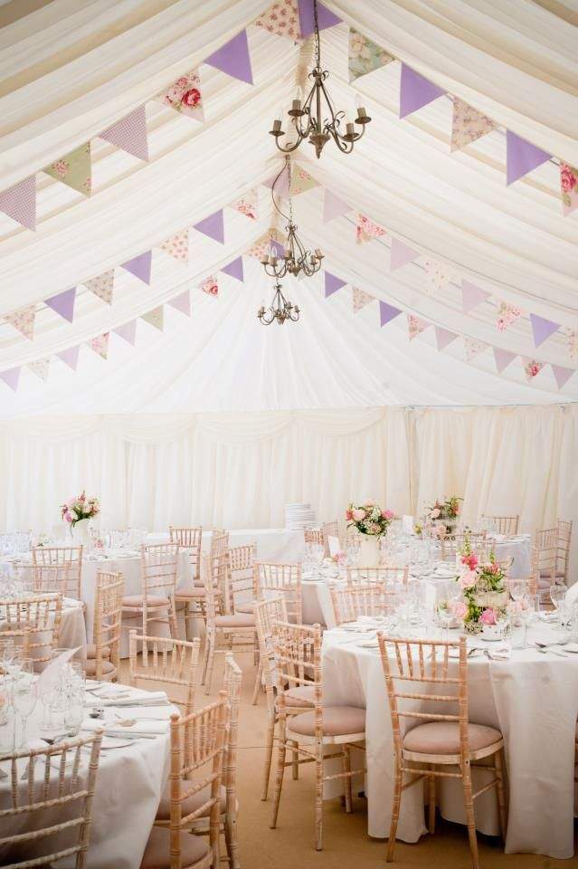 Pastel pink and white reception tent with flag decorations