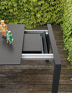 The minimalist charm of the extendible Sushi table can be seen in this outdoor version equipped with the same extension device as the indoor one, but with a 12mm thick HPL top to guarantee even higher resistance while keeping an extremely slender profile. The tray that houses the extensions is in tough thermoformed plastic, and is equipped with perforations for rainwater runoff. It has an aluminium frame with stainless steel fixings to ensure it remains unchanged over time.