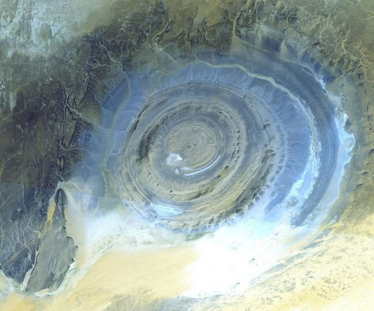 Aerial photo of richat structure.  Once thought to be an impact crater, the Richat Structure's flat middle and lack of shock-altered rock indicates otherwise. The possibility that the Richat Structure was formed by a volcanic eruption also seems improbable because of the lack of a dome of igneous or volcanic rock. Rather, the layered sedimentary rock of the Richat structure is now thought by many to have been caused by uplifted rock sculpted by erosion.