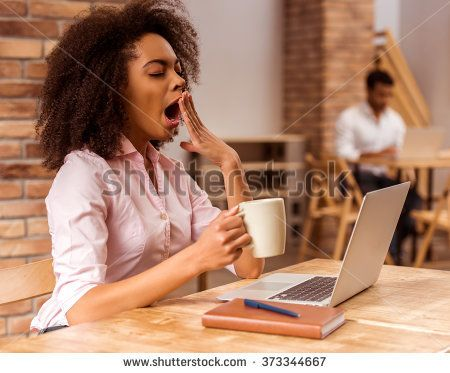 Young beautiful Afro-American businesswoman using laptop, holding cup and yawning while working in cafe