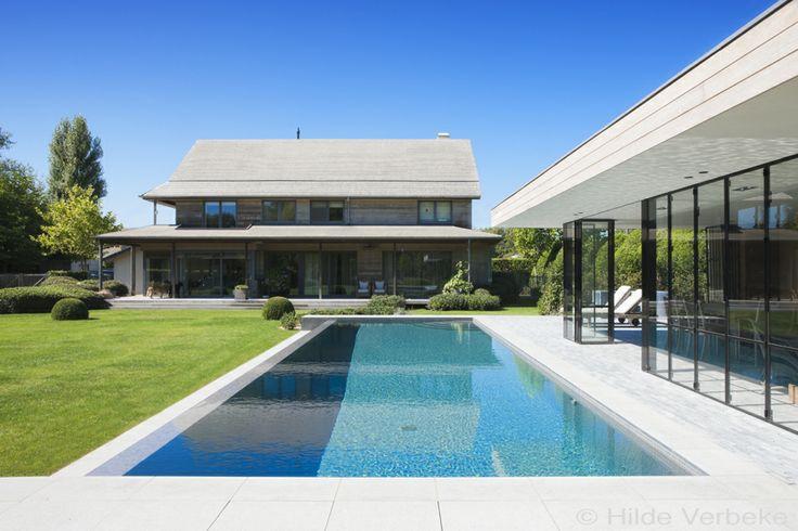 Betonnen zwembad met n overlooprand naast design poolhouse in prachtige tuin for Zwembad desing